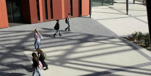 Passants traversant la cour intérieure d'un établissement d'enseignement